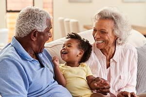 Couple with grandkid on couch with insurance planning