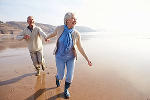 Happy elderly couple running on beach with Income planning