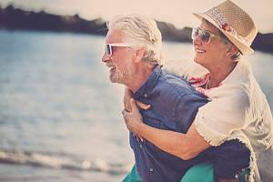 Happy older couple by lake with financial planning and analysis