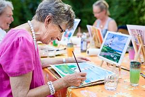 Happy woman painting in retirement because her retirement planning services
