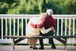 Retired couple sitting on bench thinking about retirement planning services