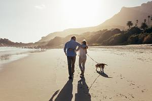 Retired couple with dog walking on beach with Legacy planning