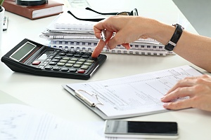 a person planning their income tax with paper and calculator to get a nice return