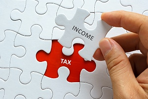 a person putting income tax puzzle pieces together