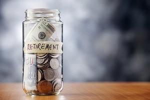 A jarful of coins and bills with retirement labeled on it. Retirement planning primarily involves financial planning