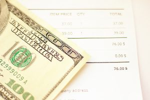 A 100 dollar bill and a payment invoice. Financial planning can overcome from paycheck-to-paycheck mentality