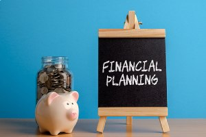 A jar full of coins, piggy bank and chalkboard with financial planning written on it
