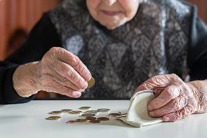 An elderly woman counting coins from her purse. Financial planning for retirement can minimize tax liabilities
