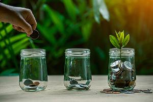 Coins in glass jar set on wooden plates depicting financial Planning concept