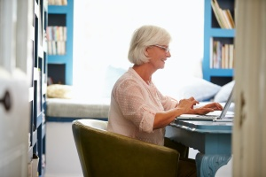 senior woman at her desk looking up retirement income planning