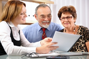older couple with a consultant looking at their retirement goals