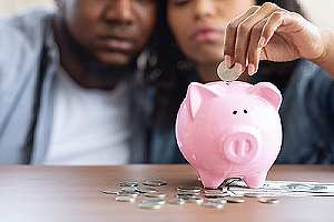 Couple putting coin on piggy bank. Panning for taxes in retirement concept