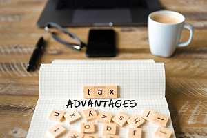 Closeup on notebook with letters making Tax advantages text. Taxes in retirement concept